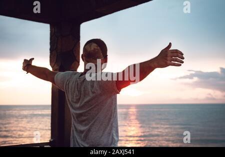 Hombre que abre sus brazos a la vista del mar y encuentra paz. Concepto De Libertad.