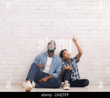 Padre e hijo sentados en el piso cerca de la pared de ladrillo blanco, apuntando y mirando hacia arriba Foto de stock