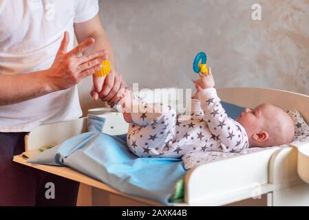 papá le da a su hijo recién nacido un masaje de pies de bola de goma