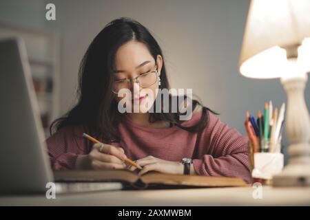 joven asiática estudiando en casa