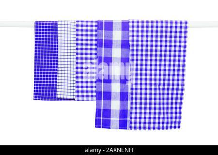 Toallas colgadas aisladas. El primer plano de varias toallas de cocina azules a cuadros cuelgan en un riel de ropa aislado sobre un fondo blanco.