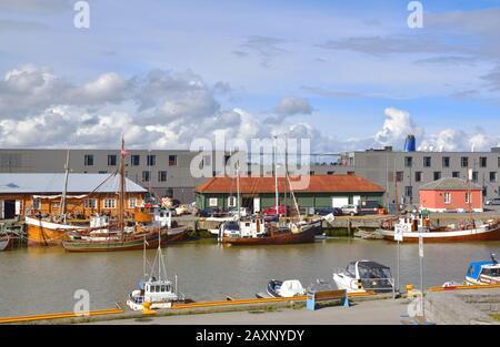Barcos amarrados a lo largo de la orilla del río Nidelva en Trondheim, Noruega. P-Hotels Brattora está en el fondo.