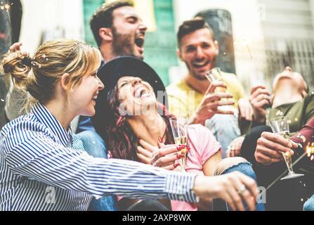 Felices amigos celebrando con los fuegos artificiales de los ahorradores bebiendo champán al aire libre - jóvenes milenios gente haciendo fiesta fuera - jóvenes, amistad y t