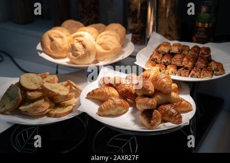 El croissant y el pan en papel y el plato blanco en la oscuridad están decorados con luz de tungsteno de la lámpara.