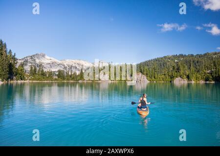 Mujer activa remos de pie sobre el paddle en el lago azul.