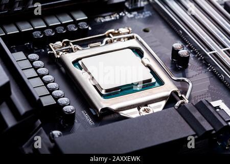 Tapa de CPU en blanco, cubierta de zócalo procesador de ángulo de visión colocado y bloqueado en el zócalo en una nueva placa base moderna de alta productividad para juegos