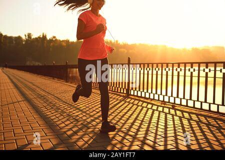 Runner corre en la carretera en el sol al atardecer en un parque de otoño.