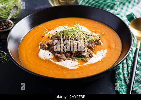 Deliciosa crema de calabaza con fórcemeat asado hecho de carne picada de ternera en un Bol en una mesa oscura. Día De Acción De Gracias.