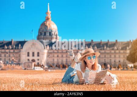 Asiática feliz niña viajero posando en la plaza cerca de los Invalides En París. Estilo de vida y turismo en Francia