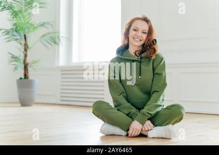 Tiro horizontal de feliz deportista de pelirroja en chándal verde, sneakers blancas, se sienta en posición de loto, tiene una sonrisa amable en la cara, posado interior. Mujer