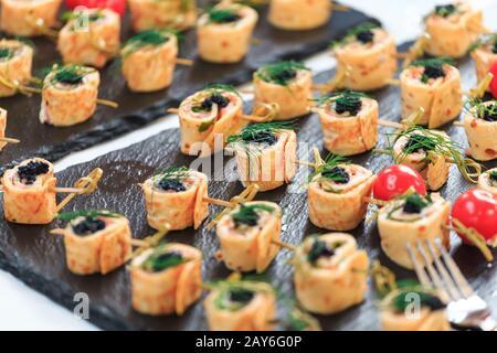 Surtido de aperitivos y canapés en un plato durante un descanso para tomar café en un seminario de negocios Foto de stock