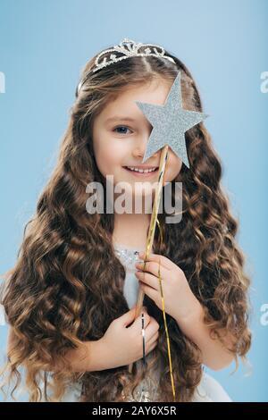 Imagen aislada de la mujer curly hermosa satisfecho con los ojos azules, cubre cara con varita mágica, tiene pelo rizado largo, poses sobre fondo azul, suave