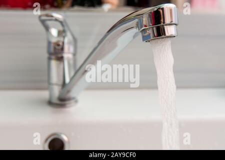 El agua fluye más presión desde el mezclador en el baño