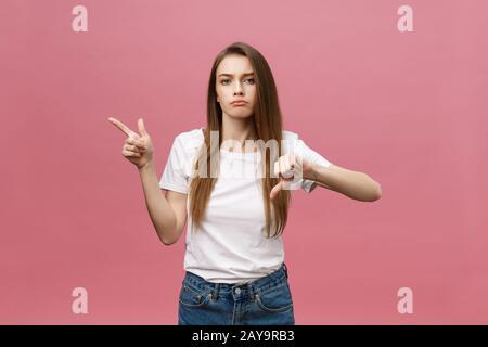 Primer plano de una estricta grave joven viste camisa blanca parece estresado y apuntando hacia arriba con el dedo aislado sobre fondo de color rosa
