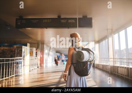 Viaje temático transporte público. Mujer joven de pie con espalda vestida y sombrero detrás de mochila y equipo de camping para dormir
