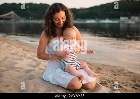 Madre joven sentada en la playa con un hijo de un año. Niño que se jovía, sonriendo, riendo, día de verano. Careffr feliz de la niñez