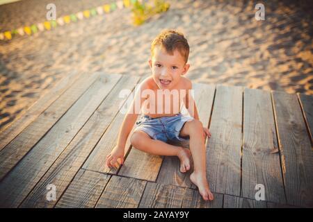 El tema son las vacaciones de playa para niños y verano. Un pequeño niño caucásico se sienta de lado en un muelle de madera y admira la vista de los s.