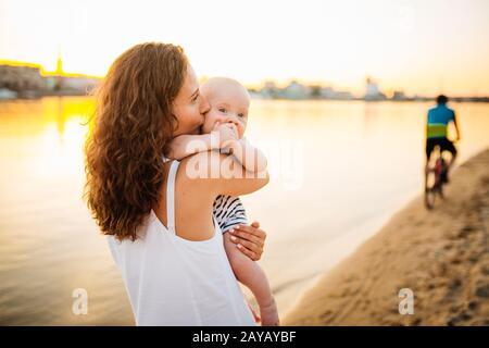 Feliz familia en la playa. Hijo niño madre niño y bebé que se acerca a la playa cerca del río o el lago. Feliz familia en la playa. Mamá y.