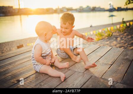Dos niños pequeños sentados en el muelle a orillas del río. Concepto de amistad y fraternidad. Soleado y alegre día de verano. Niños s Foto de stock