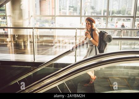 Retrato Smiling Mujer Usando sombrero En el aeropuerto En Escalator. Personas viajando con equipaje de mano. Turismo temático y transporte. Cau
