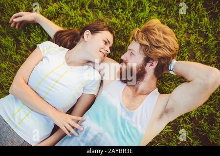 El tema es el deporte y un estilo de vida saludable. Un joven y una pareja de mujeres están descansando sobre sus espaldas en la hierba verde, un césped