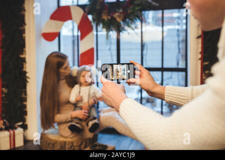 Tema de fotografía móvil, fotografía amateur y vídeo en el teléfono. Manos el hombre caucásico sostiene utiliza smartphone hace foto de la madre y.