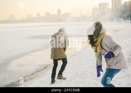 Los jóvenes caucásicos enamorados de la pareja heterosexual tienen una cita en invierno cerca de un lago congelado. Vacaciones activas San Valentín