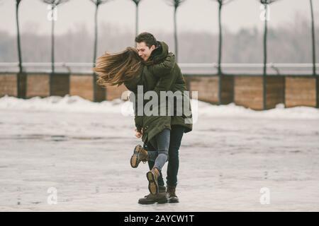 Una pareja heterosexual de jóvenes enamorados alumnas a un hombre y a una mujer caucásica. En invierno, en la plaza de la ciudad cubierta de hielo,