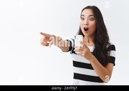 Una chica emocionada es testigo de algo extremadamente impresionante, graba vídeo en la cámara del smartphone, apuntando y mirando a los lados impresionados, jadeando, caerá la mandíbula
