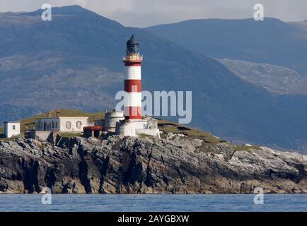 El faro alto, rojo y blanco rayado de las Glas Eileas, Scalpay, desde el mar, con las colinas de Harris detrás, las Western Islands, Escocia Foto de stock