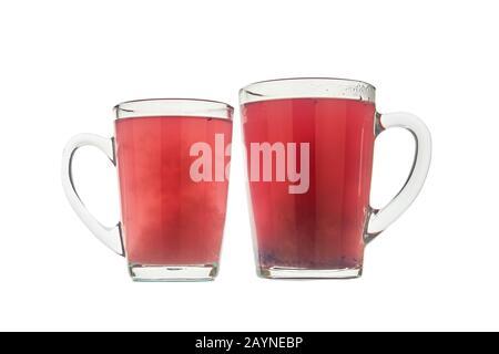 Dos vasos vacíos de cristal con té de bayas aislados sobre fondo blanco