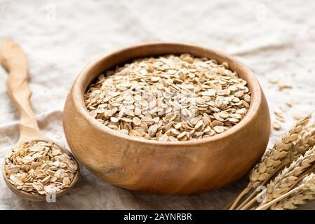 Avena enrollada, copos de avena en un tazón de madera. Comida saludable, dietas, concepto de cereales para el desayuno