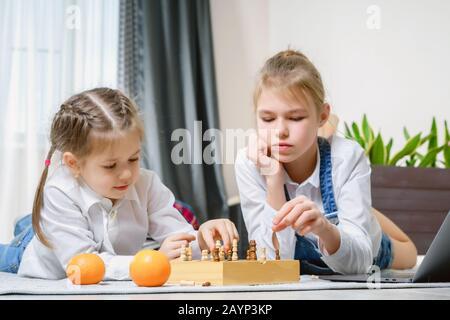 Dos hermosas hermanas jugando ajedrez en un Tablet PC.