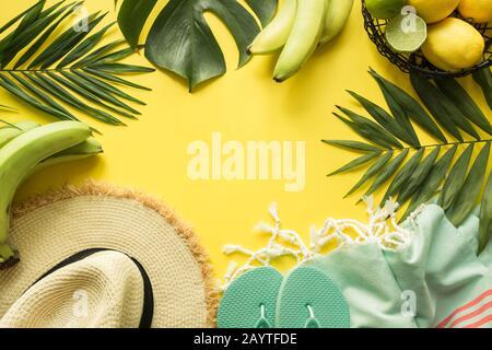 Borde de traje de playa accesorios femeninos. Vacaciones tropicales, sombrero de paja, toalla, hojas de monstera en amarillo. Concepto de verano. Vista superior con espacio fo