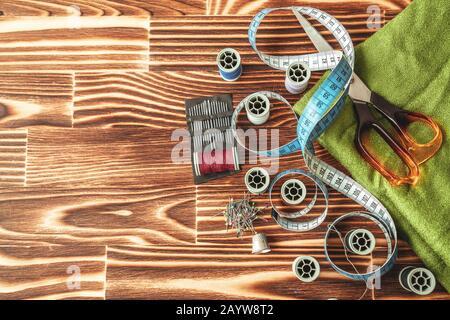Grupo de objetos sobre equipo de costura sobre fondo de madera. Concepto de costura y adaptación