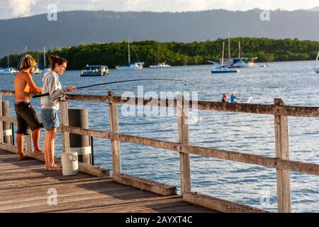 Pareja joven pescando con caña en Sugar Wharf Port Douglas, Port Douglas, Queensland, Australia