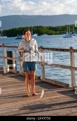 Mujer joven pescando un pez con caña en Sugar Wharf Port Douglas, Port Douglas, Queensland, Australia