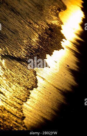 Benodet Bretaña Norte De Francia. Puesta de sol abstracta en la playa. Oro y agua. Agua reluciente y arena dorada Foto de stock