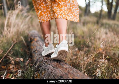 Mujer joven caminando por el bosque usando vestidos