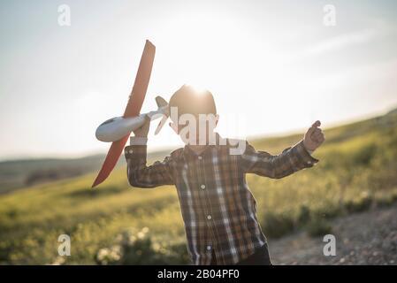 Niño pequeño con juguete avión jugando en la primavera al aire libre imagen