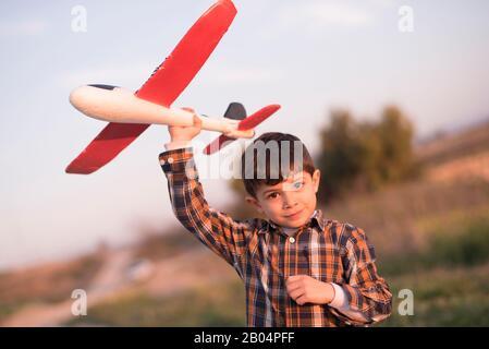 Niño pequeño con juguete avión jugando en la primavera al aire libre imagen Foto de stock