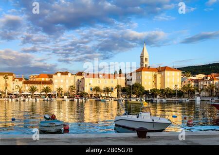 Supetar en la isla de Brac cerca de Split, Croacia. Pequeña ciudad costera con paseo marítimo y puerto con barcos blancos, palmeras, cafés, casas e iglesia. Touri