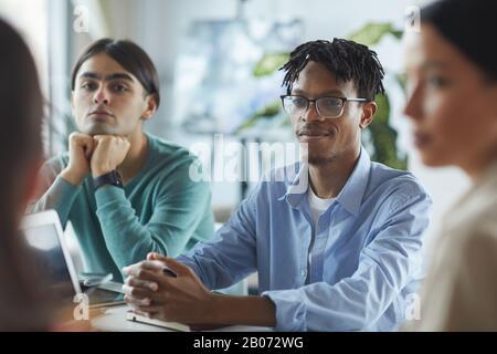 Joven empresario africano en gafas sentado a la mesa y escuchando a sus colegas en la reunión en el cargo