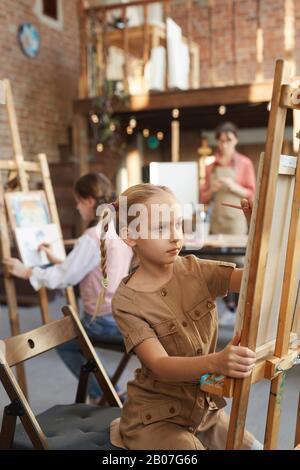 Niña sentada frente al caballete y pintando con otros estudiantes durante la lección de arte en el estudio de arte