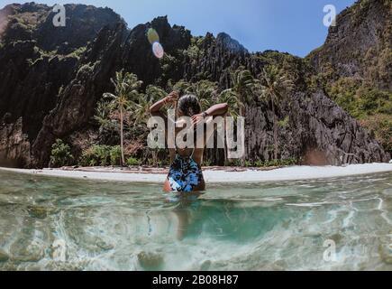 Pequeña laguna en el Nido. Mujer disfrutando del tiempo en el agua cristalina transparente, con la selva tropical en el fondo. Concepto de viajar y NAT