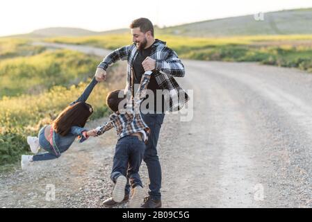 Padre rodeando en el aire sus hijos, que están suspendidos jugando al aire libre feliz