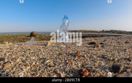 Botella de plástico en la orilla contra el telón de fondo de un arrecife de coral en marea baja. Peligro ambiental