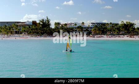 Navegación en el Mar Caribe frente a las costas de Punta Cana, República Dominicana, vacaciones de lujo y resort de vacaciones en el fondo, con arena blanca