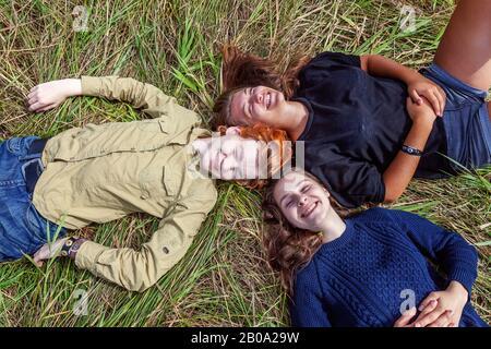 Vacaciones de verano vacaciones feliz gente concepto. Vista superior grupo de tres amigos tumbados en la hierba en círculo sonriendo y divirtiéndose juntos al aire libre. Picnic con amigos en viaje por carretera en la naturaleza