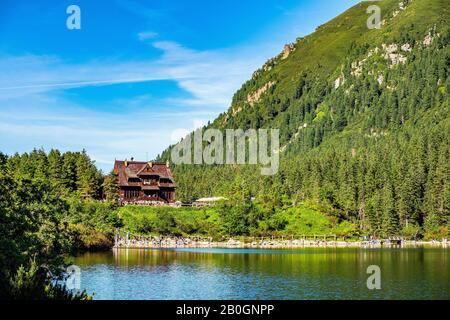 Vista panorámica del lago de montaña Morskie Oko que rodea el bosque de alerce, pino y abeto con la casa de refugio Schronisko przy Morskim Oku en el fondo